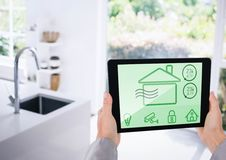 Hand holding digital tablet with home security icons on screen. In kitchen stock image