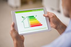 Energy efficiency house. Hand holding digital tablet and looking at house efficiency rating. Detail of house efficiency rating on digital tablet screen. Concept royalty free stock photos