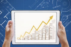 Hand holding digital tablet with raising up arrow graphs on screen, on architectural blueprint background Stock Photography