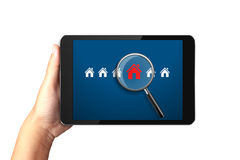 Hand holding digital tablet with Searching for house of home. On white background royalty free stock image