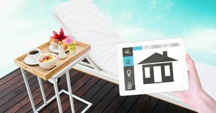 Hand holding digital tablet with smart home application on screen at poolside Royalty Free Stock Images