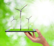 Hand holding digital tablet with a wind turbines. Royalty Free Stock Image