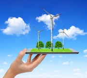 Hand holding digital tablet with a wind turbines and trees. Green energy concept Stock Photography