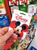 A hand holding Disney gift card. PLATTSBURGH, USA - SEPTEMBER 10, 2018: A man holding Disney gift card. Walt Disney or simply Disney, is an American diversified stock photos