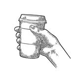 Hand holding a disposable cup of coffee with cardboard holder and cap. Royalty Free Stock Photography