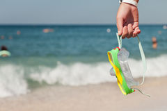 Hand holding diving goggles on sea beach royalty free stock images