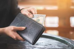 Hand holding 100 dollar bank take out from wallet royalty free stock images