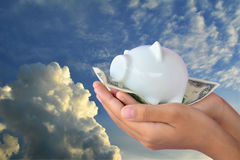 Hand holding dollar banknote and piggy bank Stock Images