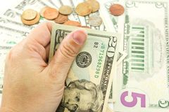 Hand holding dollar bill. Left  hand holding dollar bill with coins and dollar bill are background Stock Photography
