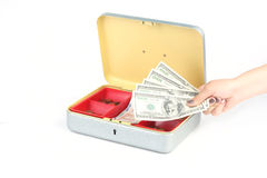 Hand holding dollars in front of money box on white Royalty Free Stock Image