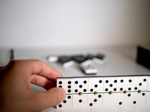 Hand holding domino. First person point of view. Concept of dominoes royalty free stock images