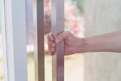 Hand holding door knob, opening door, selective focus. Hand holding door knob, opening door slightly, selective focus Royalty Free Stock Photo