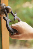 Hand holding a door knocker. Old style door holding and knocker Royalty Free Stock Photos