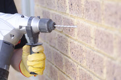 Hand holding drill at wall Stock Images