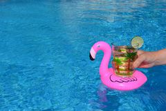 Hand holding a drink in an inflatable pink flamingo drinks holder in swimming pool stock photos