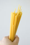 Hand holding dry noodles (bucatini) Stock Photos
