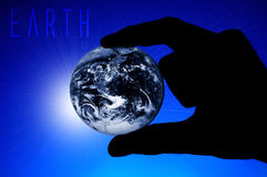 Hand holding Earth. Hand holding planet Earth, blue background and sunlight Royalty Free Stock Photos