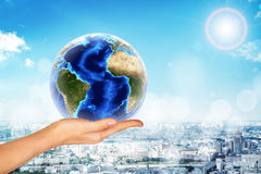 Hand holding earth globe. On city background stock photography