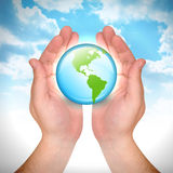 Hand Holding Earth Globe in Sky. A man's hands are holding an Earth and it is glowing. North and South America are showing on the globe and there are clouds in Stock Images