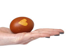 Hand holding Easter egg with heart shape on it, isolated on white Royalty Free Stock Photography
