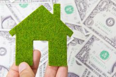 Hand holding eco house icon. Save money concept Stock Photos