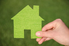 Hand holding eco house icon concept on the green grass background. Hand holding green eco house icon concept on the green grass background Stock Image