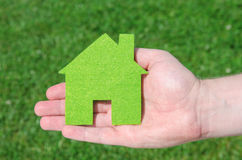Hand holding eco house icon concept on the green grass background. On a sunny day Royalty Free Stock Photography