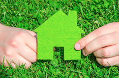 Hand holding eco house icon concept on the green grass background. On a sunny day Stock Photos