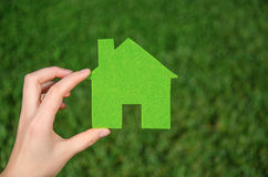 Hand holding eco house icon concept on the green grass background. On a sunny day Royalty Free Stock Images