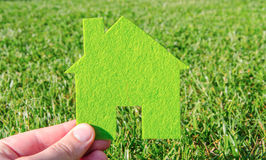Hand holding eco house icon concept on the green grass background. On a sunny day Stock Photo