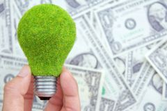 Hand holding eco light bulb on dollars background. Save money concept Stock Photos