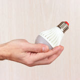 Hand holding ecofriendly led lightbulb on light wood background. Hand holding ecofriendly led lightbulb on a light wood background stock photos