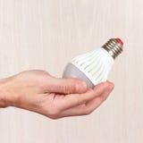 Hand holding ecofriendly led lightbulb on light wood background Stock Photos