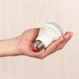 Hand holding ecofriendly led lightbulb on light wood background Royalty Free Stock Image