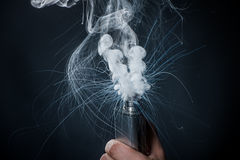 Hand holding an electronic cigarette over a dark background Royalty Free Stock Photography
