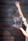 Hand holding empty birdcage Stock Photography