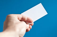 Hand holding an empty business card. On blue background Royalty Free Stock Photos