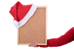 Hand holding empty frame with red santa hat Royalty Free Stock Image
