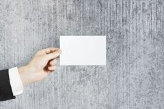 Hand holding empty visiting card. On concrete wall background. Mock up Royalty Free Stock Image