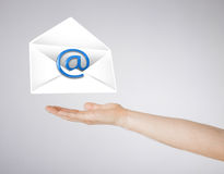 Hand holding envelope with email sign Stock Images