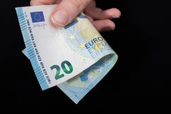 Hand holding 100 euro banknote on a black background. Hand holding 100 euro money  cash isolated on black background Royalty Free Stock Image