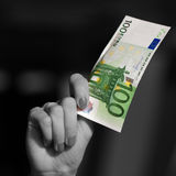 Hand holding Euro banknote. Black and white woman`s hand holding showing colorful 100 Euro banknote Stock Photos