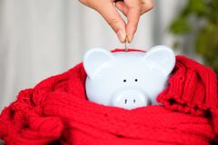 Hand holding euro coins into a piggy bank wrapped in a scarf