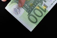 Hand holding 100 euro banknote on a black background. Hand holding 100 euro money  cash  on black background Stock Photography