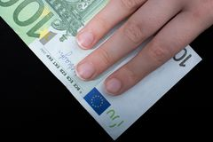 Hand holding 100 euro banknote on a black background. Hand holding 100 euro money  cash isolated on black background Stock Photos