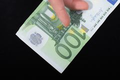 Hand holding 100 euro banknote on a black background. Hand holding 100 euro money  cash isolated on black background Royalty Free Stock Images