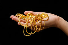 Hand Holding Expensive Gold Jewelry. Necklace and bracelet royalty free stock images
