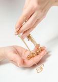 Hand Holding Expensive Gold Jewelry. On a white background royalty free stock photos