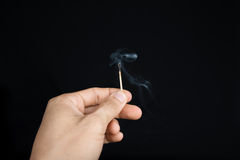 Hand holding an extinguished matchstick on black background Stock Image