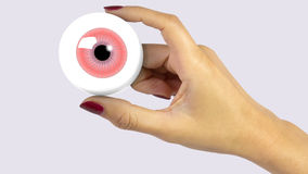 Hand holding eyeball. Woman's hand with red fingernails holding a red eyeball illustration Royalty Free Stock Photo